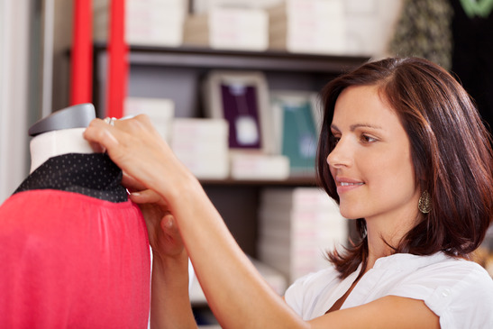 Saleswoman Examining Clothes On Mannequin